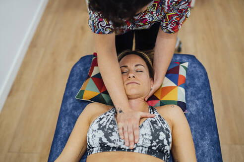 Female osteopath giving chest massage to sportswoman lying in medical clinic - SASF00050