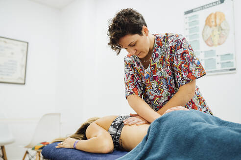 Female osteopath therapist giving back massage to sportswoman at health spa - SASF00056