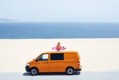 Young woman sitting on top of van and looking at sea during summer vacations - JCMF01316