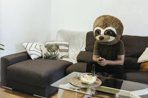 Man wearing teddy bear mask watching TV while sitting on sofa against wall at home - XLGF00485