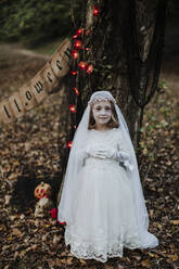 Little girl standing while wearing corpse bride costume against tree in forest - GMLF00544