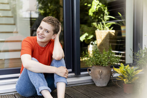 Smiling beautiful woman with hand in hair sitting outside house - UUF21294