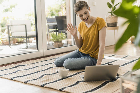 Cheerful woman waving while video conferencing over laptop on carpet at home - UUF21315