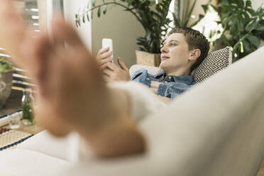 Thoughtful mid adult woman with smart phone resting on sofa in living room - UUF21345
