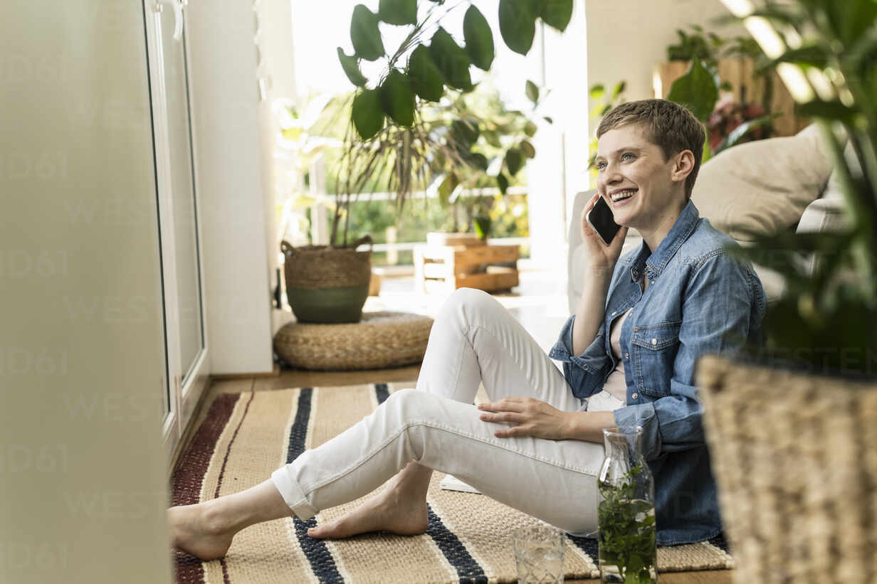Cheerful woman talking over smart phone while sitting on carpet at home - UUF21348 - Uwe Umstätter/Westend61