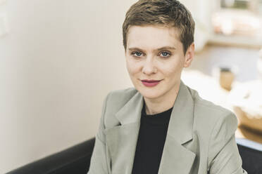 Close-up of confident businesswoman with short hair sitting at home - UUF21360