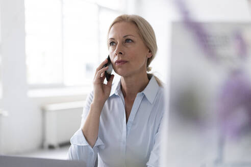 Confident businesswoman talking over mobile phone while sitting in home office - MOEF03211