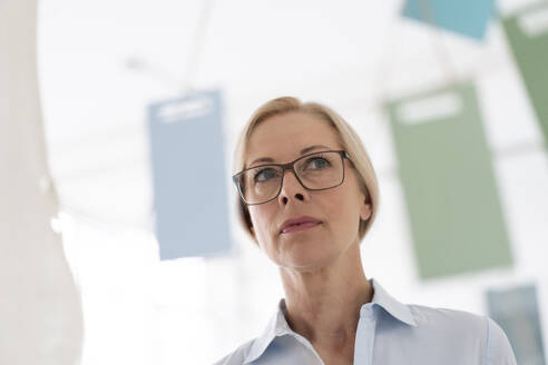 Close-up of thoughtful businesswoman wearing eyeglasses looking away in home office - MOEF03217