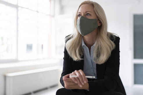 Businesswoman wearing face mask looking away while standing in home office - MOEF03238