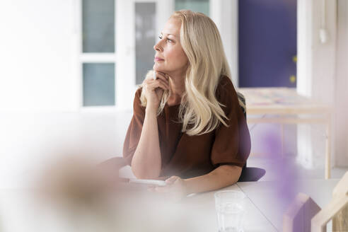 Thoughtful mature woman looking away while sitting in home office - MOEF03271