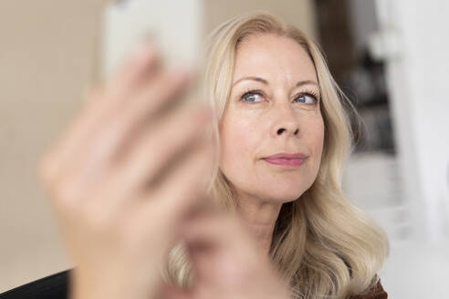 Close-up of beautiful businesswoman taking selfie with smart phone in office - MOEF03274