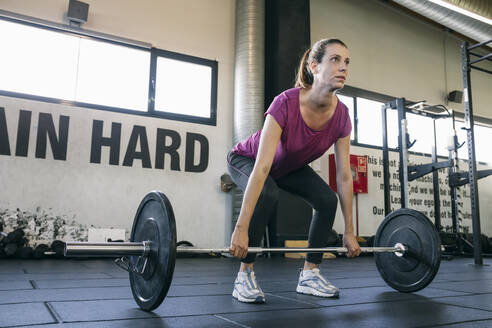 Female athlete lifting deadlift while standing in gym - ABZF03279