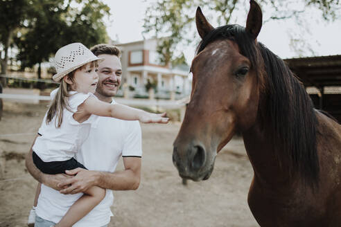 Father carrying daughter touching horse while standing outdoors - GMLF00570
