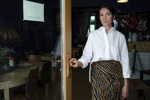 Portrait of female owner standing at entrance in coffee shop - OGF00525
