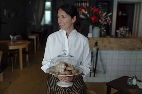 Smiling female owner holding cookies in plate with cloche at cafe - OGF00537