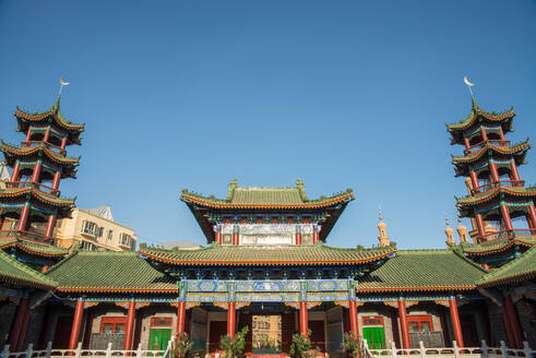 Low angle of exterior of oriental building with curved roof and ornamental pagodas on background of cloudless sky - ADSF15209