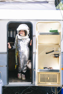 Girl wearing space suit standing at entrance of motor home - JCMF01361