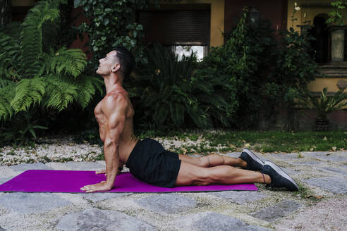 Shirtless male athlete practicing cobra pose on mat against plants - EBBF00696