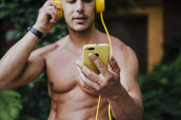 Close-up of shirtless man listening music through headphones while standing in yard - EBBF00699