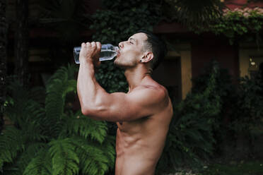 Shirtless male athlete drinking water while standing against plants in yard - EBBF00702