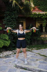 Smiling mid adult woman lifting weights while standing in yard - EBBF00705