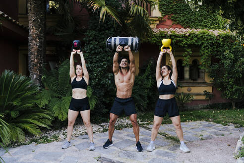 Male fitness instructor with women lifting weights while standing in yard - EBBF00714
