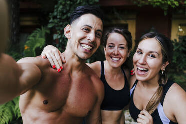Close-up of shirtless man with cheerful female friends standing in yard - EBBF00717