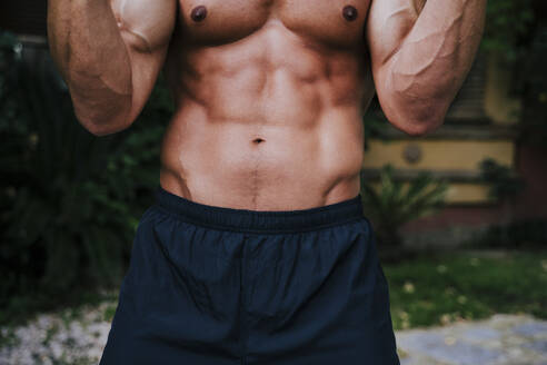 Close-up of shirtless muscular man exercising in yard - EBBF00720