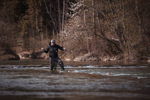 Fly fisherman holding fishing rod while casting in flowing river at forest - DHEF00382