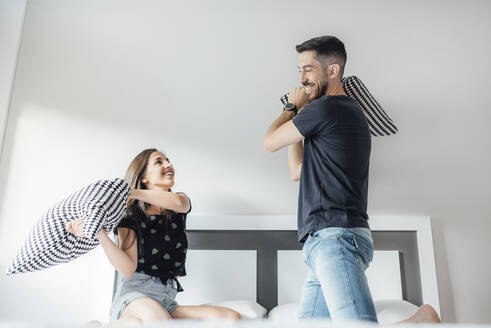 Happy couple having pillow fight on bed in bedroom at home - SASF00076