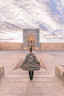 Back view of female in ornamental coat standing on aged square against cloudy sky in Bukhara, Uzbekistan - ADSF15254