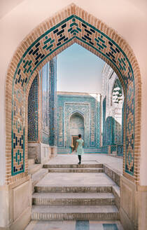 Back view of female traveler walking in arched passage of old building during trip in Uzbekistan - ADSF15275