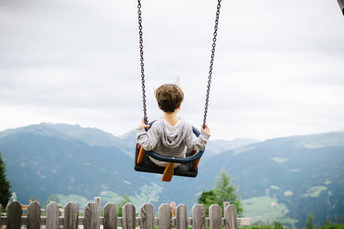 Back view of active kid swinging high in countryside on background of breathtaking mountains in cloudy day - ADSF15278
