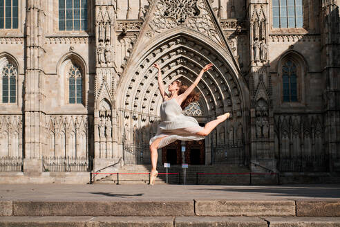 Full body of young female ballet dancer performing sensual dance moves and jumping with arms raised against ornamental stone building with Gothic architecture - ADSF15326