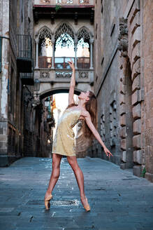 Full body of graceful young female dancer in pointe shoes performing elegant dance with arm raised on narrow paved passage against aged stone building - ADSF15329