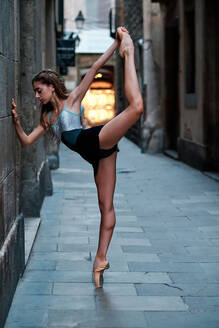Full body side view of slim young ballerina in dress and pointe shoes performing graceful ballet pose against weathered wall of aged stone building on street of old city - ADSF15332