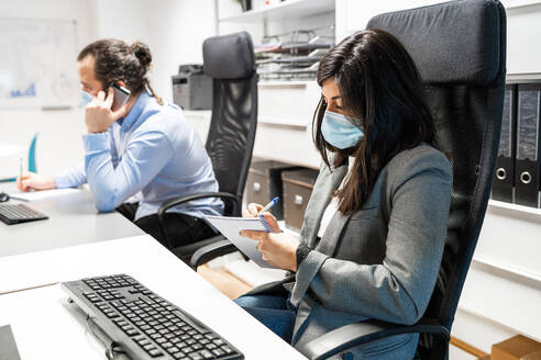 Serious young female employee in formal clothes and protective mask sitting at desk with computer and writing in notebook while working in contemporary workspace with colleague - ADSF15356