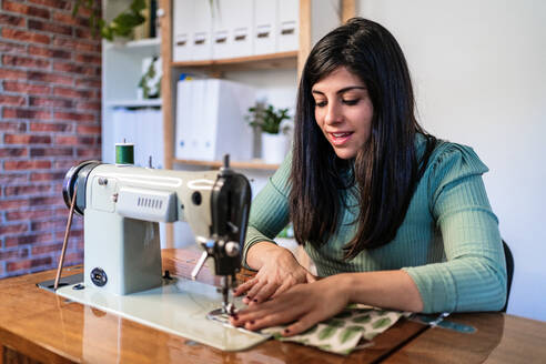 Craftswoman using modern sewing machine while creating soft fabric samples with creative green pattern near lamp in loft style workshop - ADSF15362