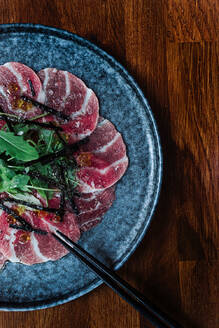 From above of slices of carpaccio slices on plate garnished with green herbs in cafe on black background - ADSF15380