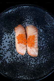 Top view of appetizing fish sushi garnished with caviar and served on plate in restaurant - ADSF15383