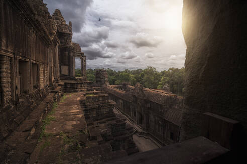 Weathered exterior of historic Angkor Wat complex against cloudy sky in Cambodia - ADSF15386