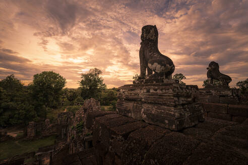 Spectacular scenery of traditional Buddhist temple with monuments of animals on background of magnificent sundown in Cambodia - ADSF15392