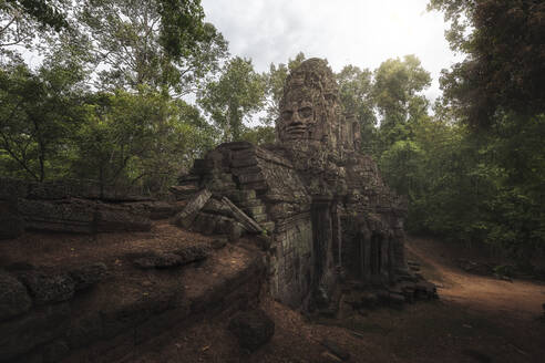 Low angle of wonderful scenery of aged Buddhist temple covered with huge tree roots and located in jungles in Cambodia - ADSF15395