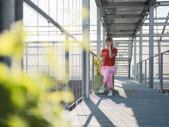Businesswoman talking over smart phone while sitting on footbridge in greenhouse - JOSEF01631