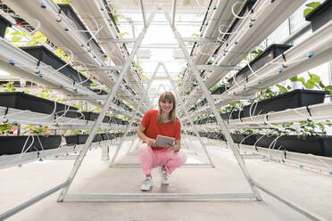 Smiling businesswoman with digital tablet crouching on floor in greenhouse - JOSEF01634