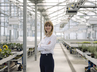 Smiling businesswoman with arms crossed standing in greenhouse - JOSEF01637