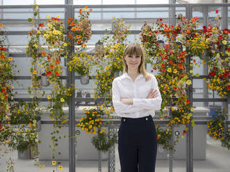 Smiling businesswoman with arms crossed standing against flowers in greenhouse - JOSEF01643