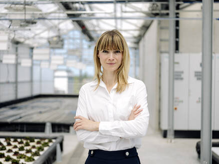 Smiling female owner with arms crossed standing in plant nursery - JOSEF01652