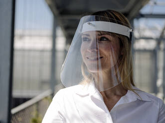 Close-up of businesswoman wearing face shield looking away in greenhouse - JOSEF01661