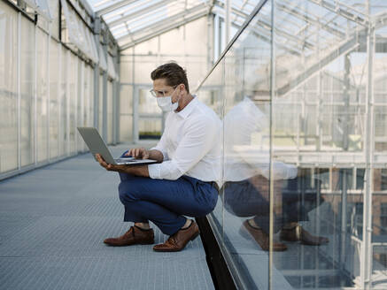 Businessman wearing mask using laptop while crouching on floor in greenhouse - JOSEF01685
